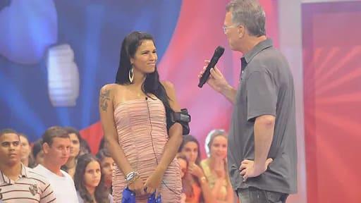Cena do programa Big Brother Brasil, quando Ariadna foi eliminada. ela está de vestido rosa, em pé, cabelos soltos e é entrevistada por Pedro Bial, que usa camisa e calças cinza