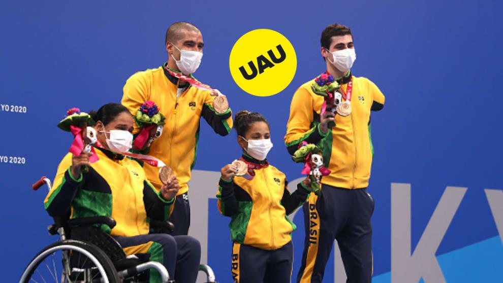 """Equipe do time de revezamento 4x50, segurando suas medalhas de bronze, e um selo com os dizeres: """"UAU""""."""