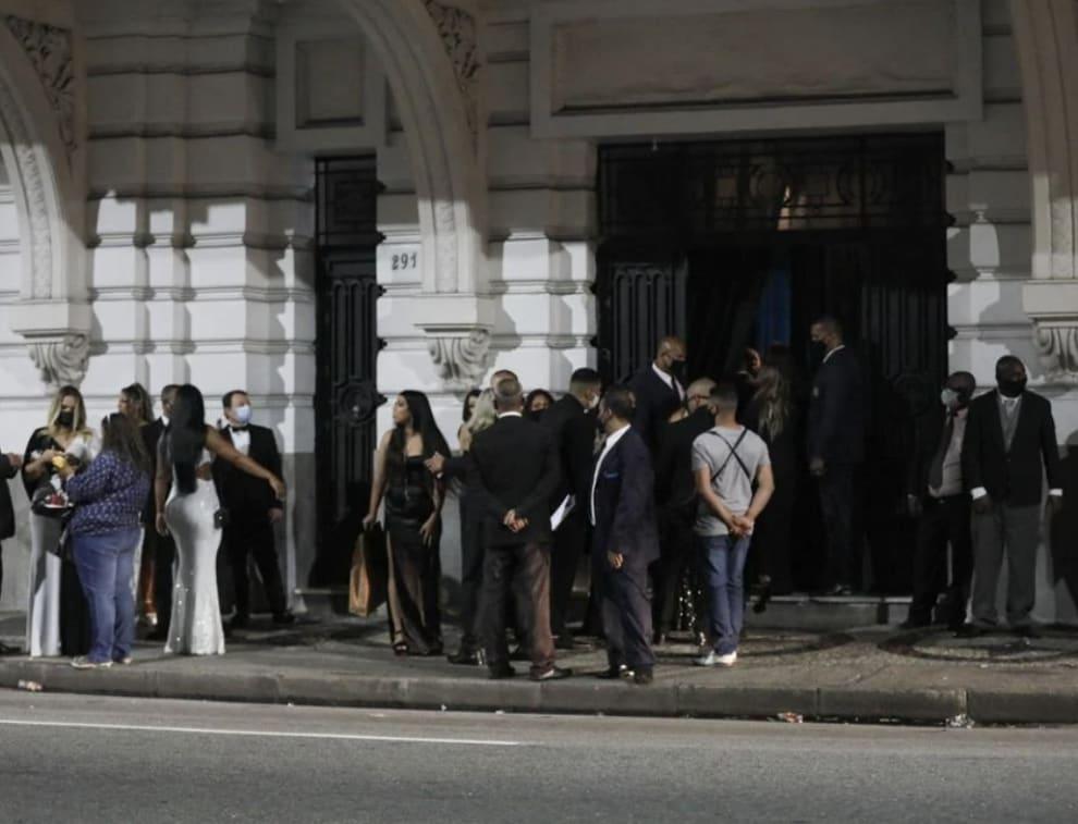 Mais imagens de convidados aglomerados na porta do hotel.