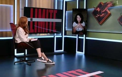 A Apresentadora Ana Clara conversa com Ariadna, a eliminada da semana do 'No Limite' por vídeo conferência. Ana Clara está sentada de pernas cruzadas. Atrás dela há uma TV onde se lê 'No Limite'. Em sua frente, em uma outra TV, aparece a imagem de Ariadna.