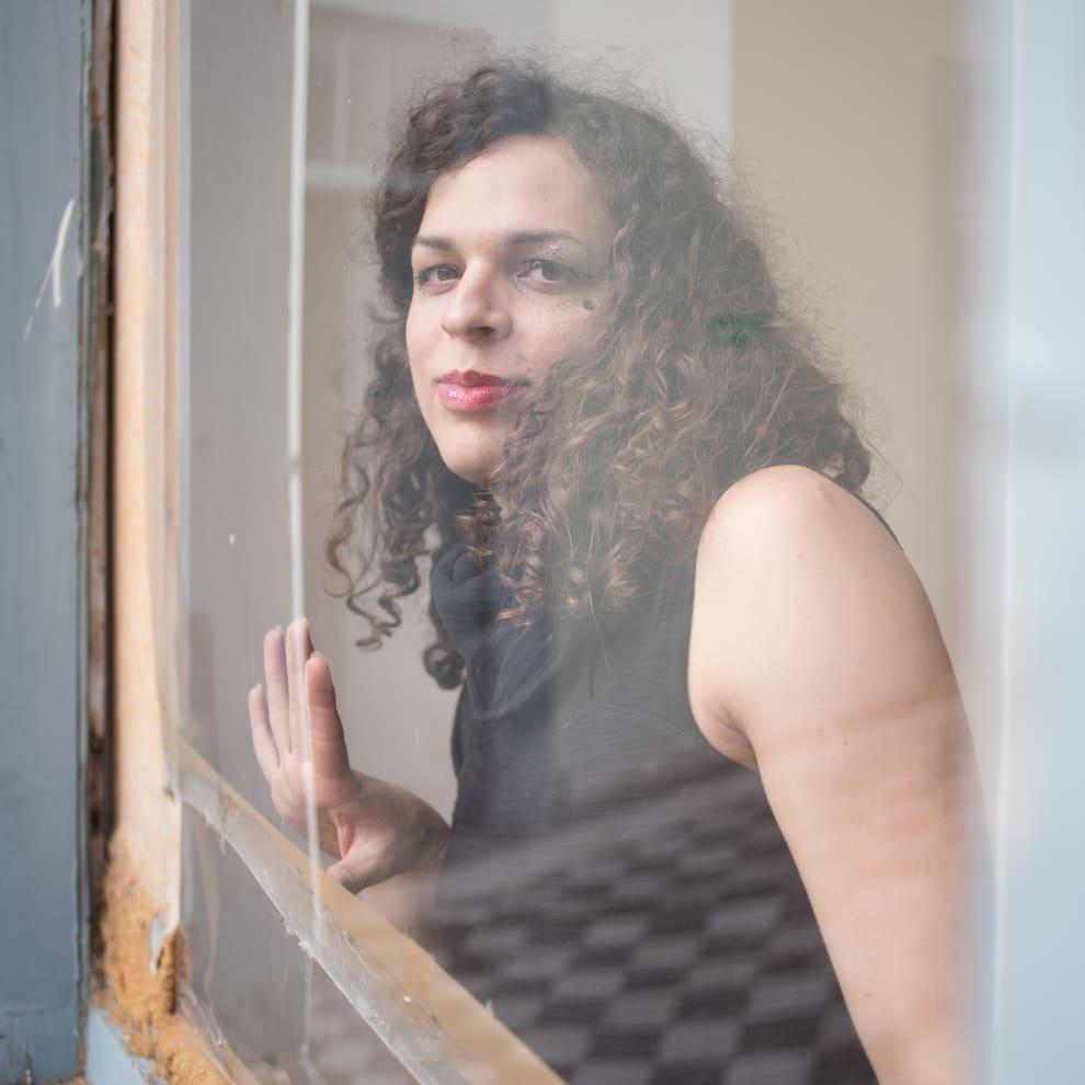 Amara Moira, de cabelos castanho cacheados, usando um vestido preto, está atrás de um vidro, apoiando a mão sobre ele e olhando diretamente pra câmera com uma expressão serena.
