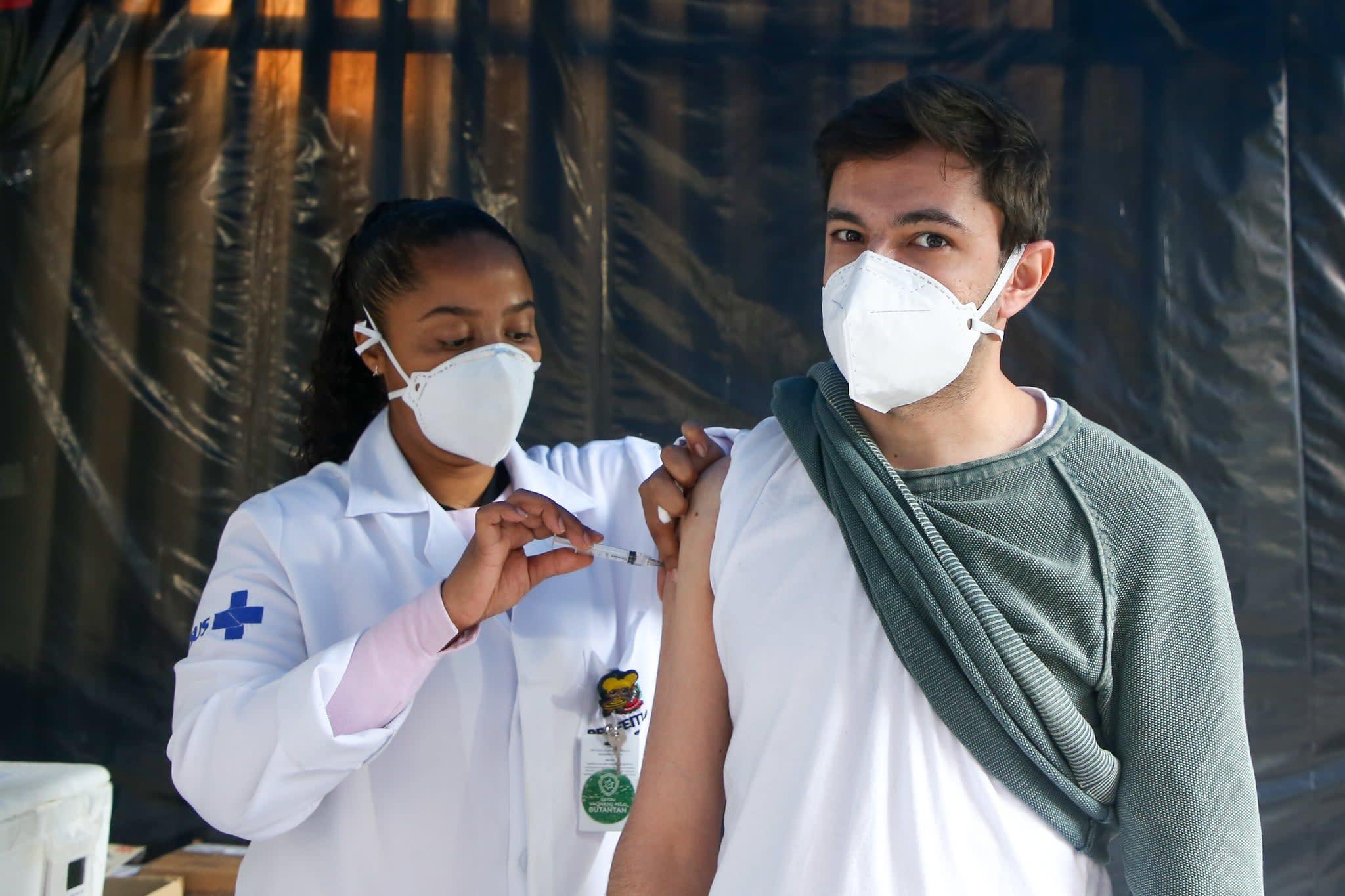 Homem jovem sendo vacinado em São Paulo