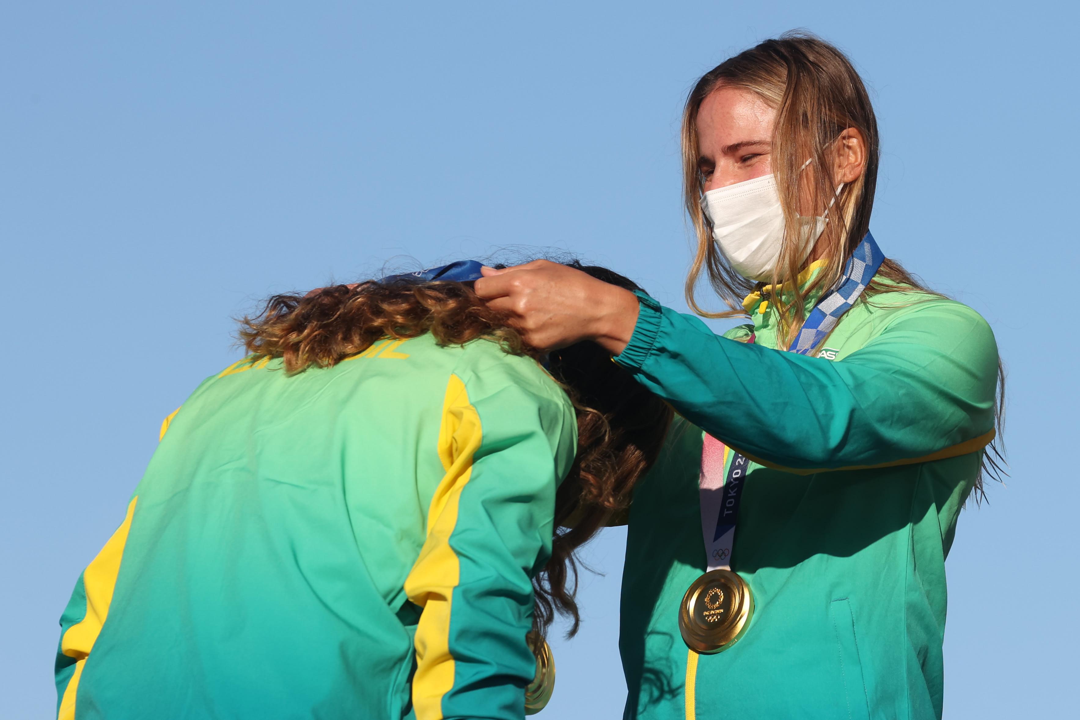 Uma atleta colocando a medalha na outra.