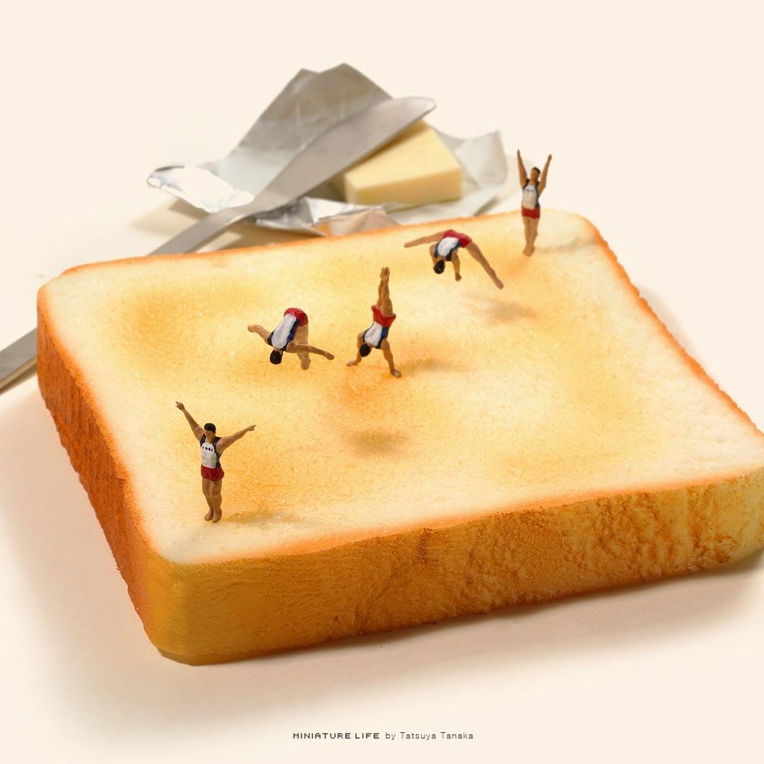 Um pão serve de tatami de ginástica olímpica para várias miniaturas enfileiradas, simulando o movimento de um ginasta