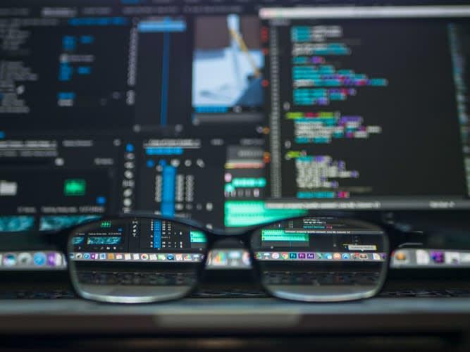 Oculos na frente de tela com códigos de computador