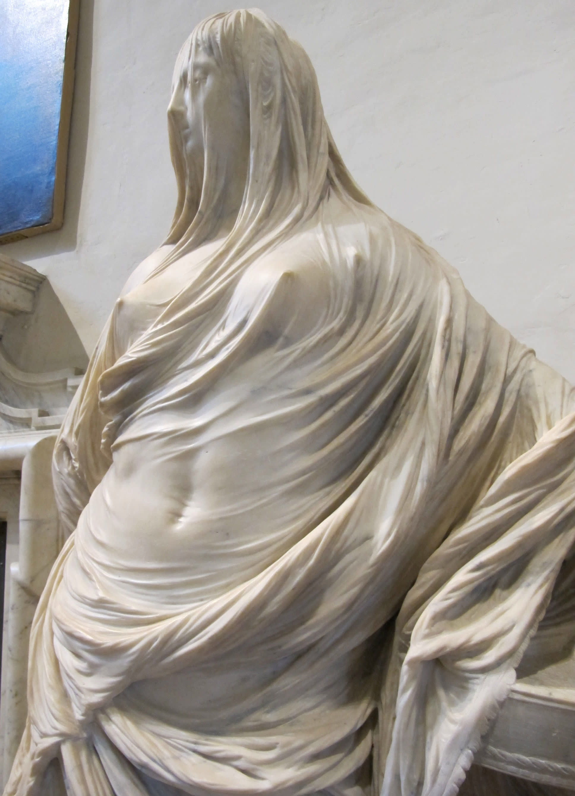 Escultura simula uma mulher nua coberta por véus