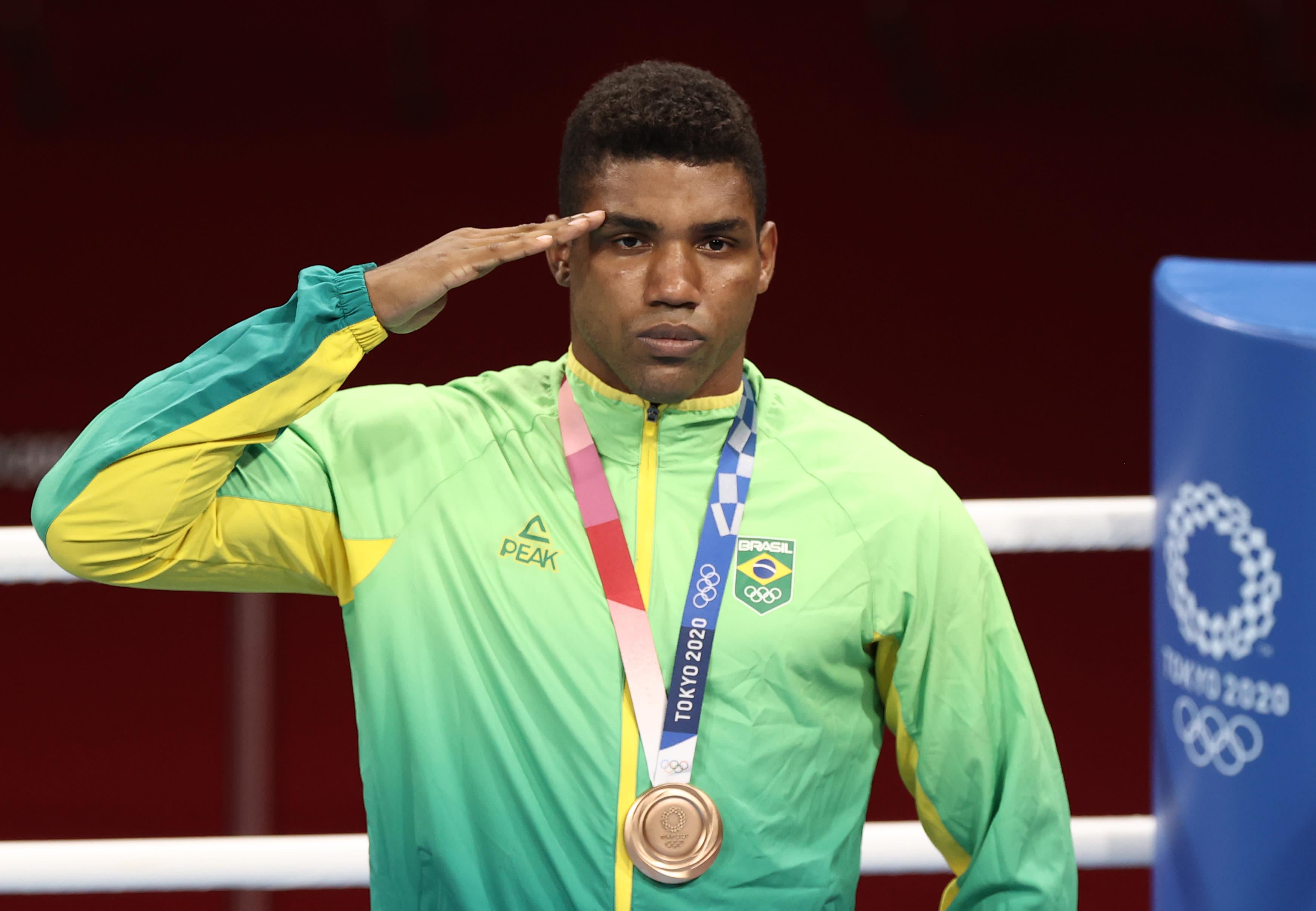 Abner batendo continência, com a medalha de bronze no peito.