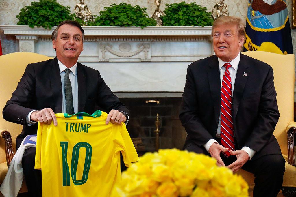 Bolsonaro segurando uma camiseta da seleção com o nome de Trump, que sorri ao seu lado