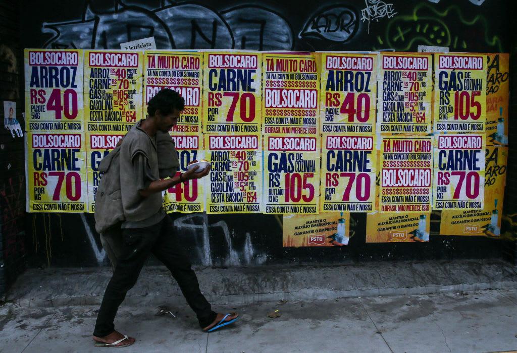 Pessoa em situação de rua passando em frente à postêres criticando Jair Bolsonaro pelo aumento do preço dos alimentos