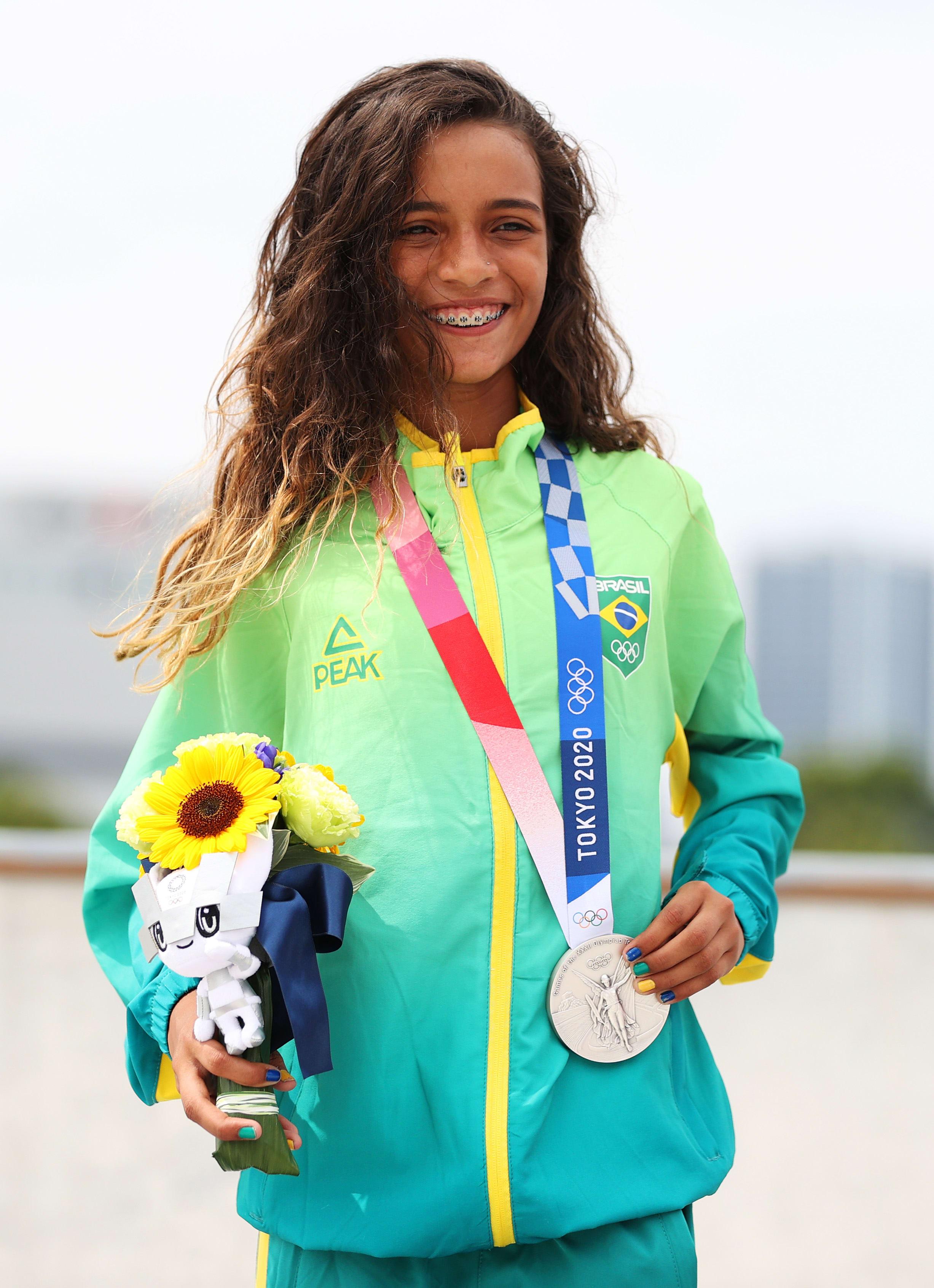 Rayssa segurando a medalha e um buquê que vem acompanhado de um bichinho de pelúcia.