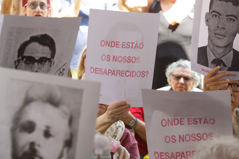 """Pessoas segurando fotos com rostos e placas com o texto """"onde estão os nossos desaparecidos?"""""""