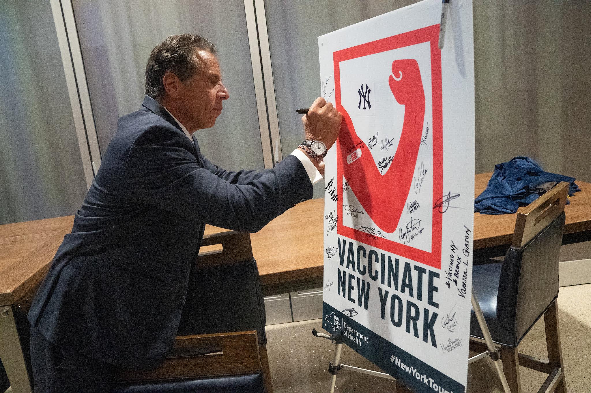 Andrew M. Cuomo, governador de Nova York, autografando um poster de vacinação.