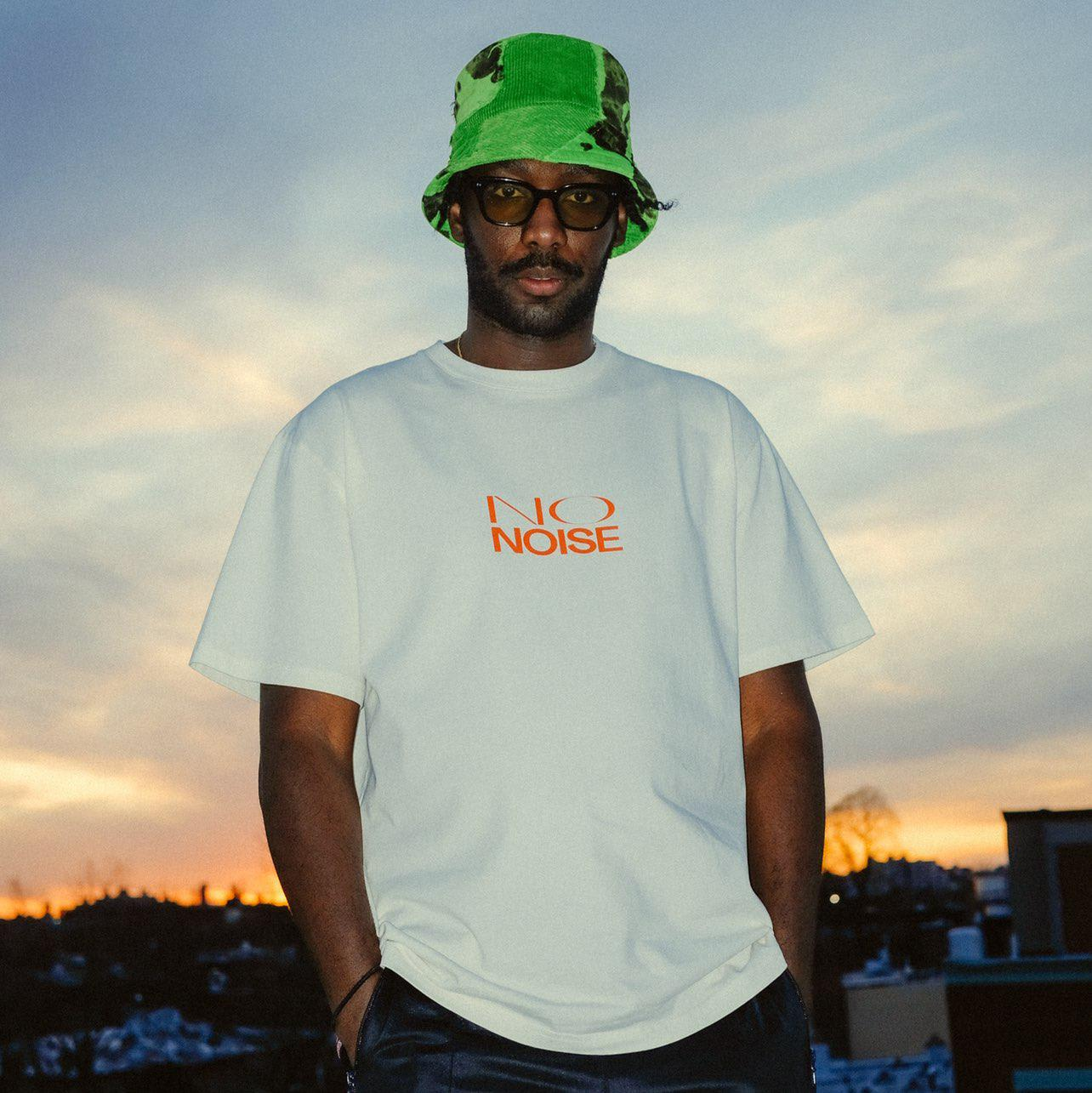 """Homem negro usando óculos com lentes amarelas, chapéu verde e camiseta branca escrita """"No Noise"""""""