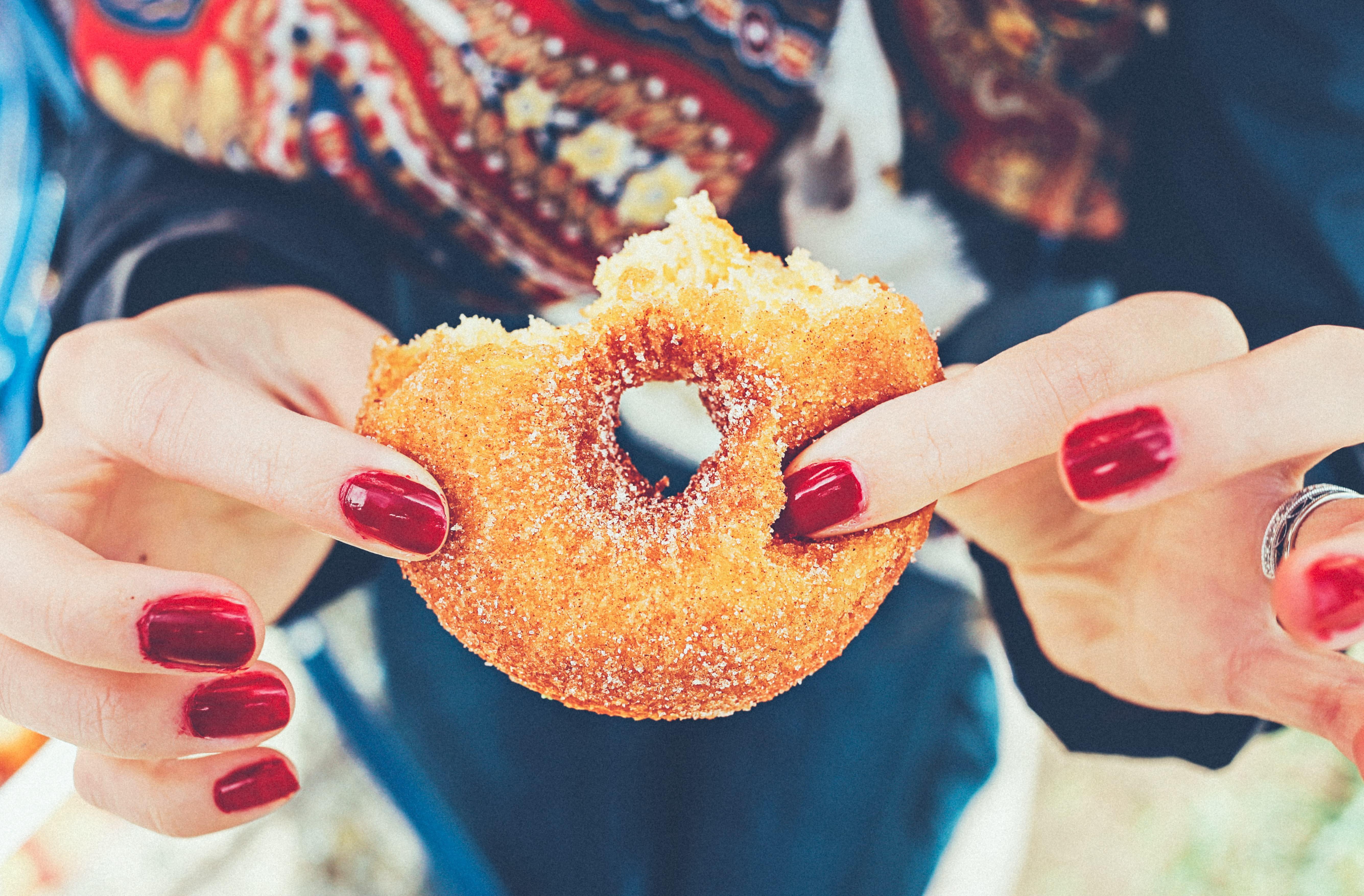 mãos femininas segurando um donut comido