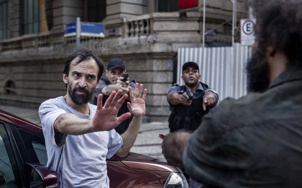 Dr. Evandro com um homem apontando uma arma para ele. Dois policiais militares são vistos atrás.