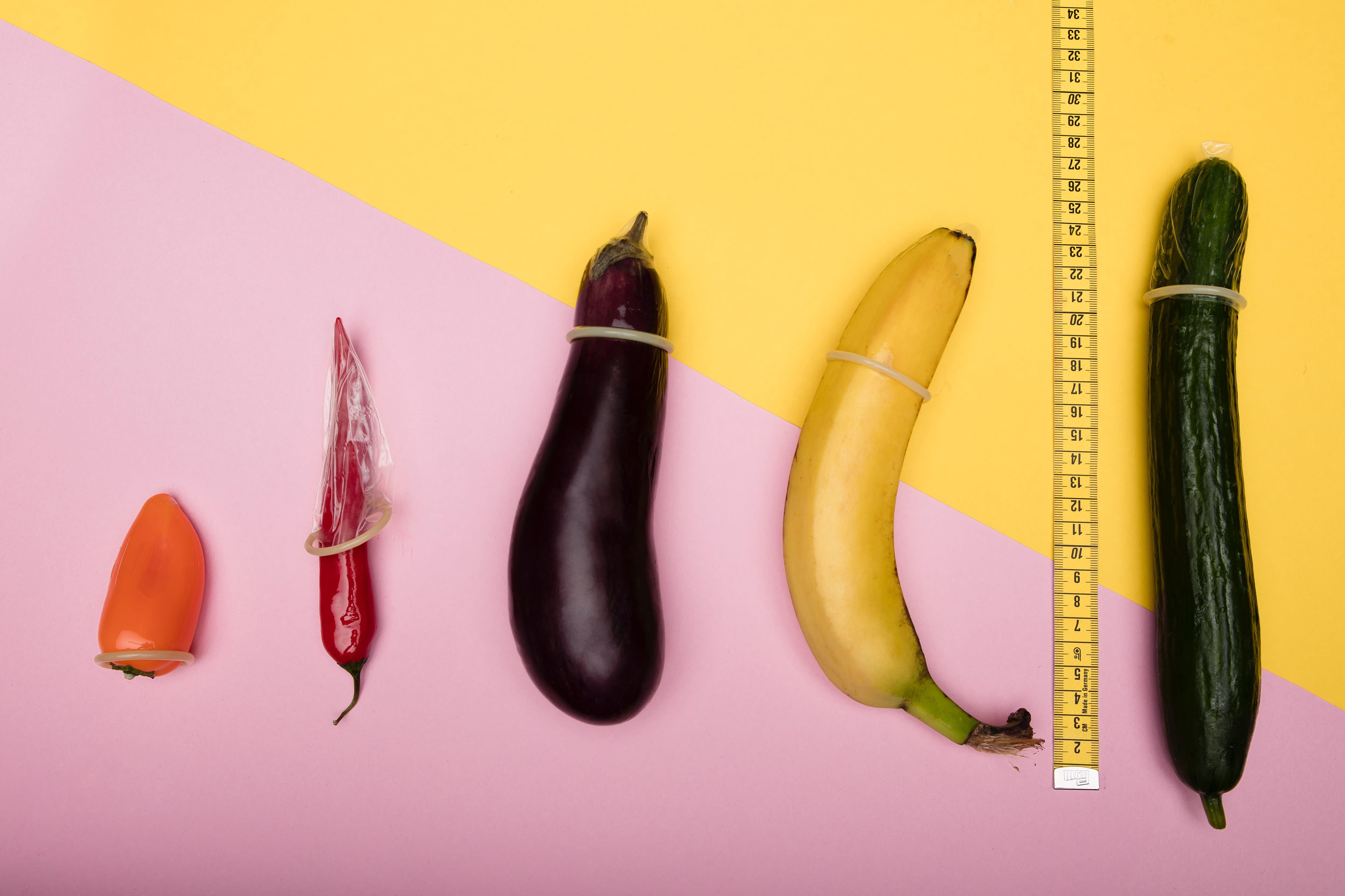 Vários legumes com camisinhas: berinjelas, pimentas, pepinos, bananas, e uma fita métrica no meio deles.