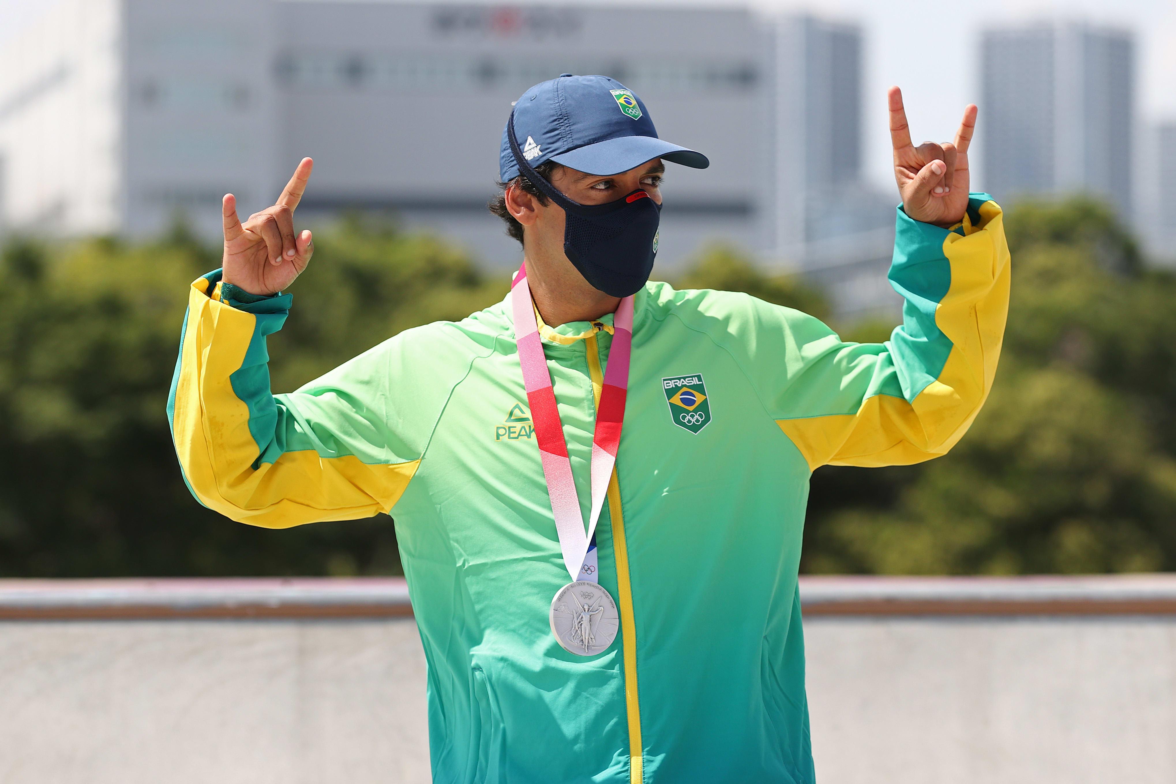 Kelvin fazendo o sinal de rock N roll, enquanto veste sua medalha de prata.