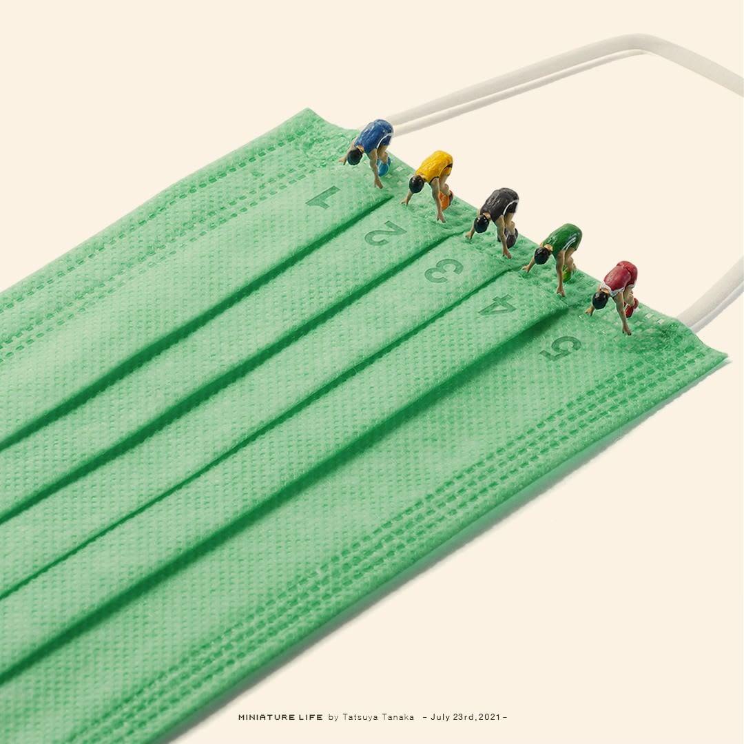 Bonequinhos que parecem prontos para correr sobre uma máscara verde - que lembra um gramado.