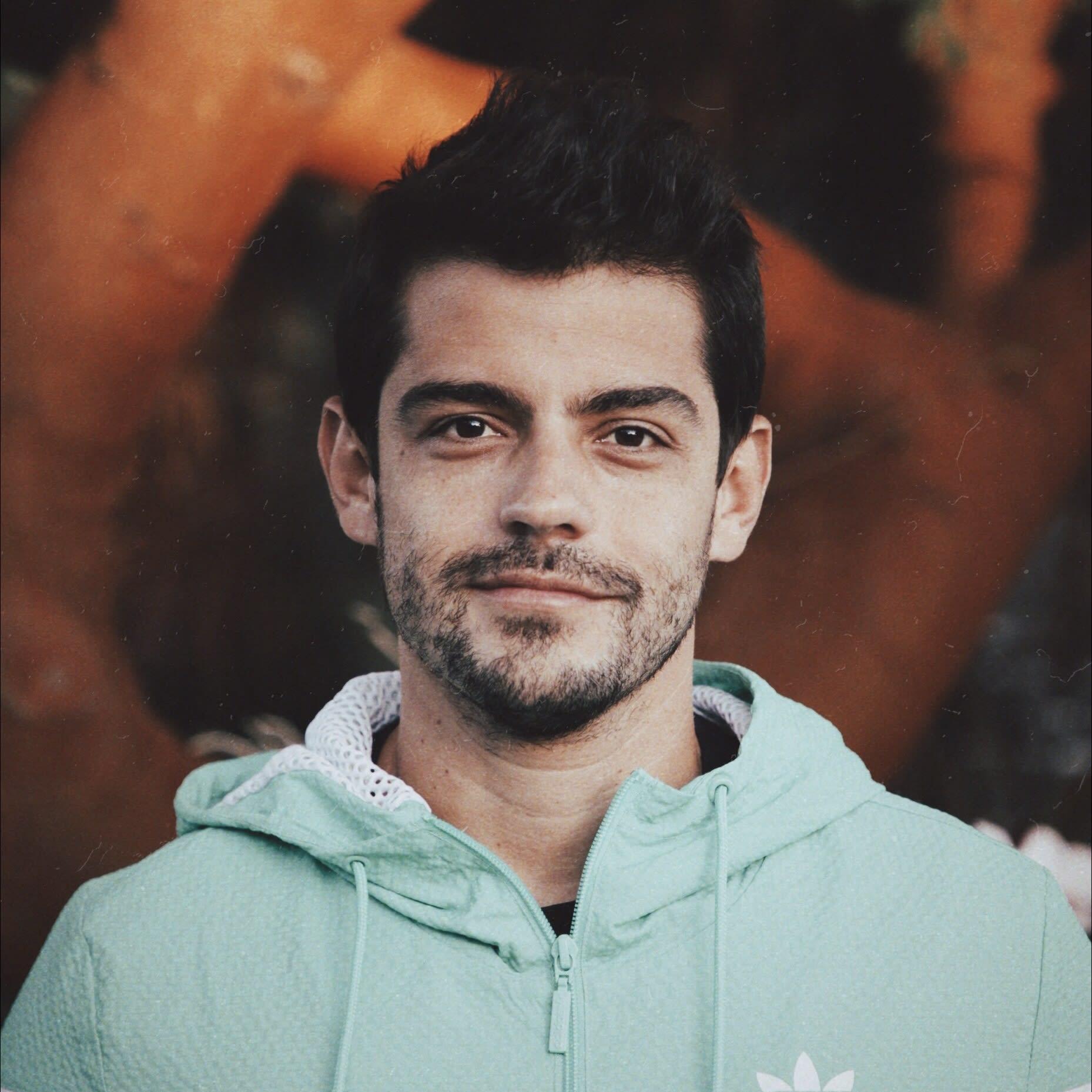 Raphael Pavan está de frente para a câmera, sorrindo de canto. Está vestindo um agasalho verde claro.
