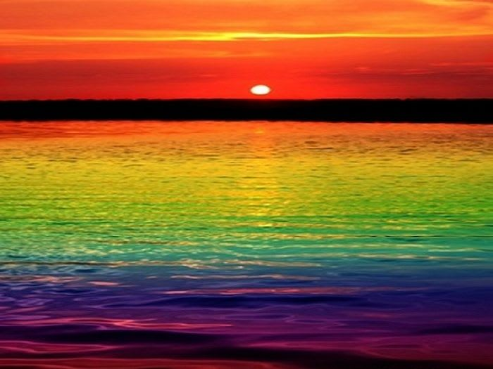 Pôr do sol refletindo a bandeira LGBTI+ no mar.