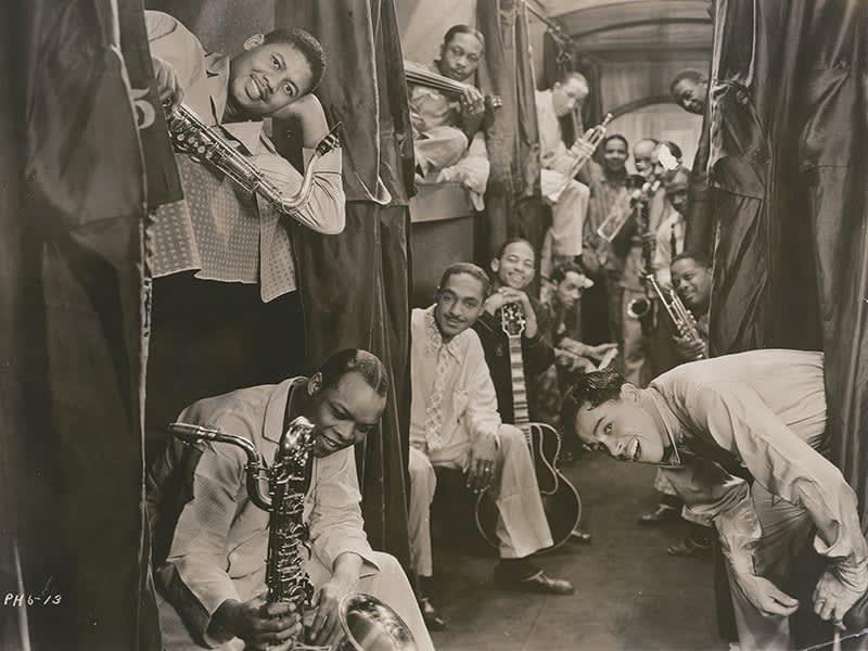 Foto antiga em preto e branco. Diversos homens negros sorriem enquanto cada um deles segura um instrumento musical.