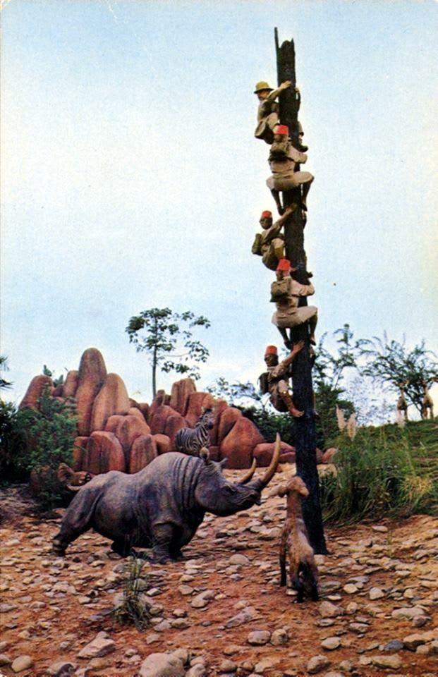 Estátua de um rinoceronte e uma hiena perseguindo guias que sobem em um tronco