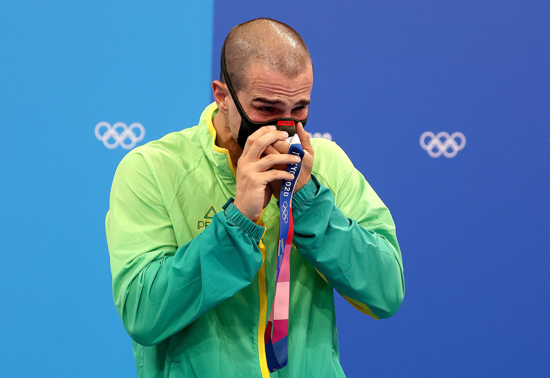 Bruno beijando a medalha de bronze sob a máscara, enquanto chora.