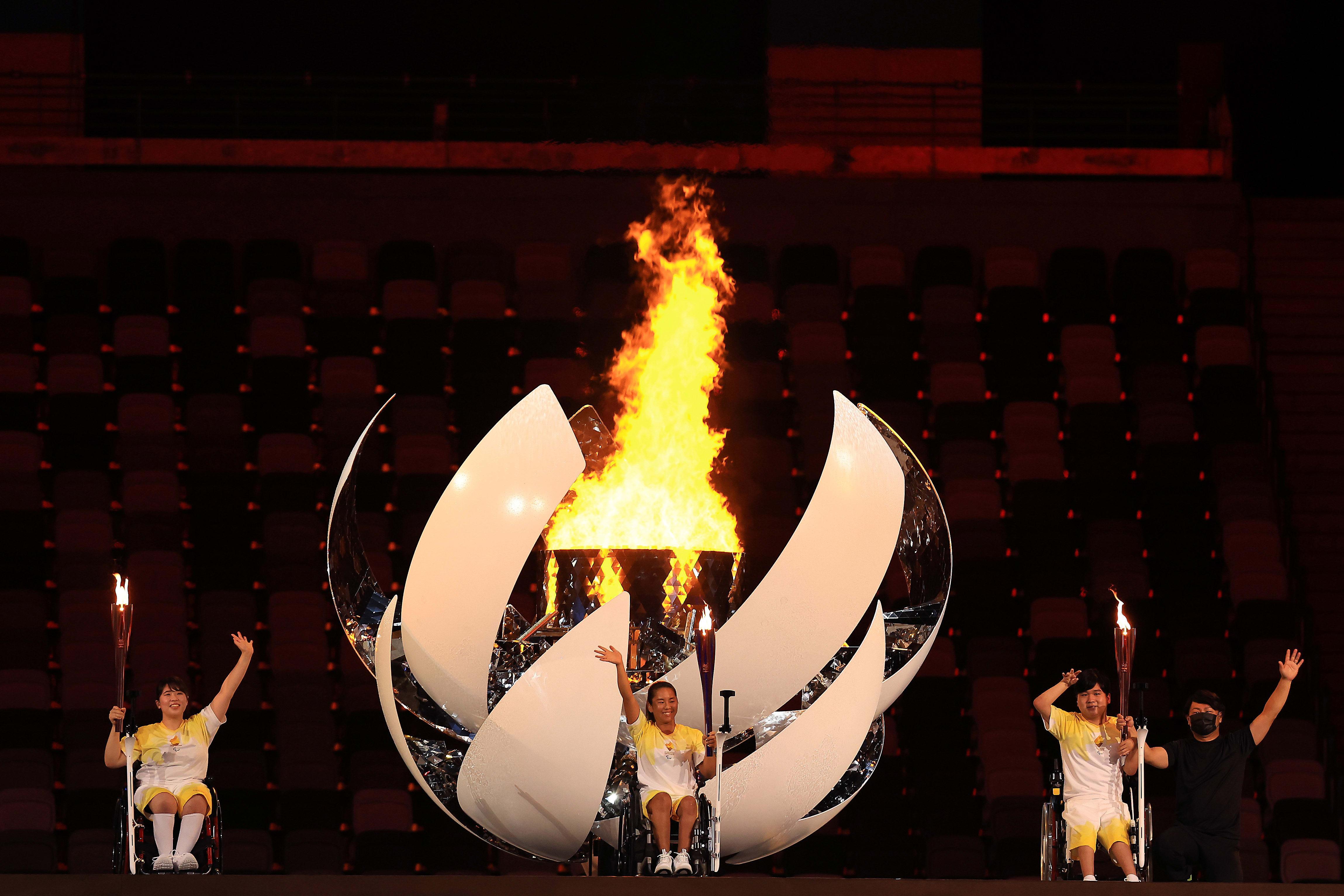 Três atletas japoneses em frente à pira olímpica.