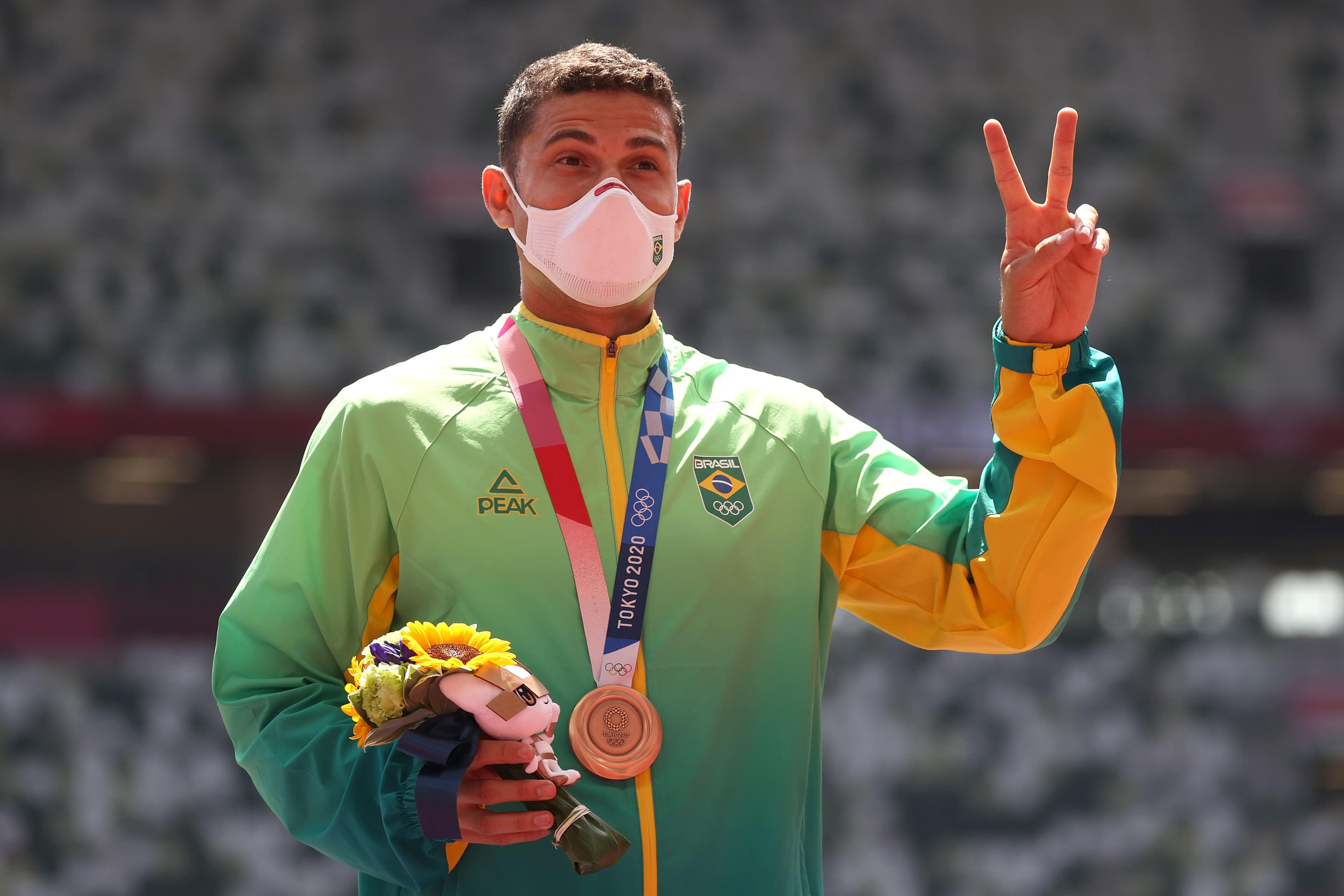 Thiago fazendo o sinal de vitória com a medalha de bronze no peito.