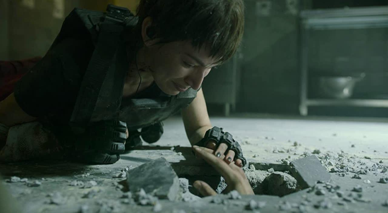 Tóquio olhando, marejada, para uma mão que sai de um buraco no chão.