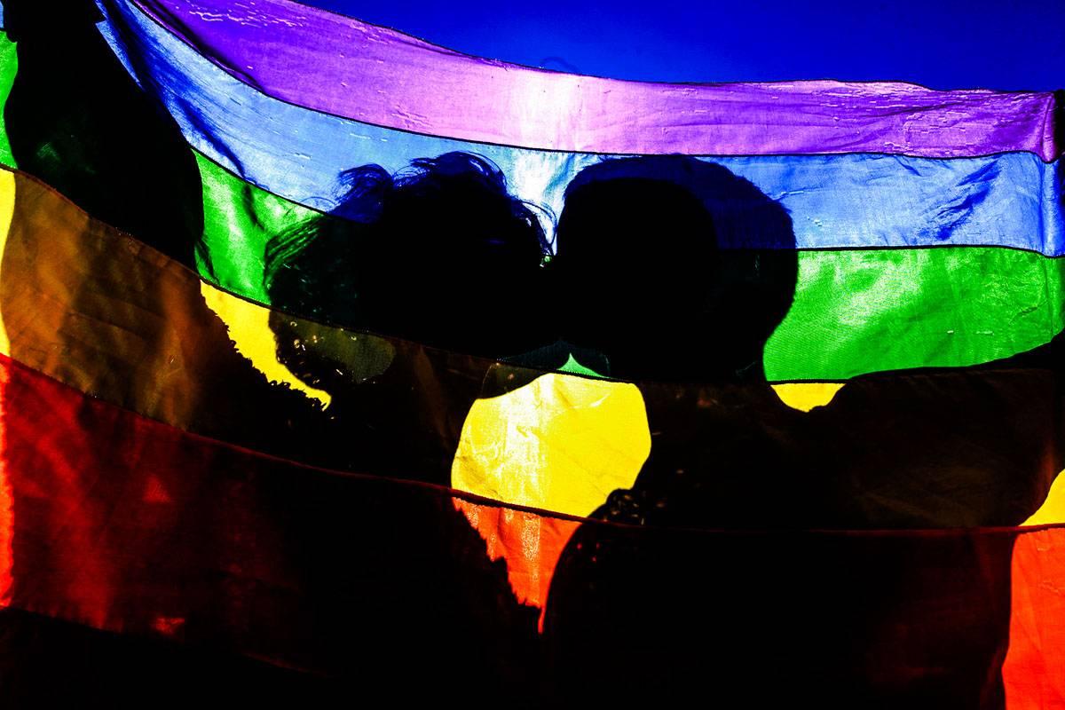 Dois homens se beijam atrás de uma bandeira do arco-íris