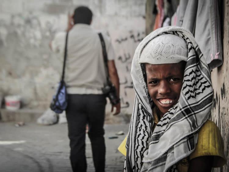 Jovem negro palestino sorri para a foto. Ele usa camiseta amarela e lenços cobrindo sua cabeça