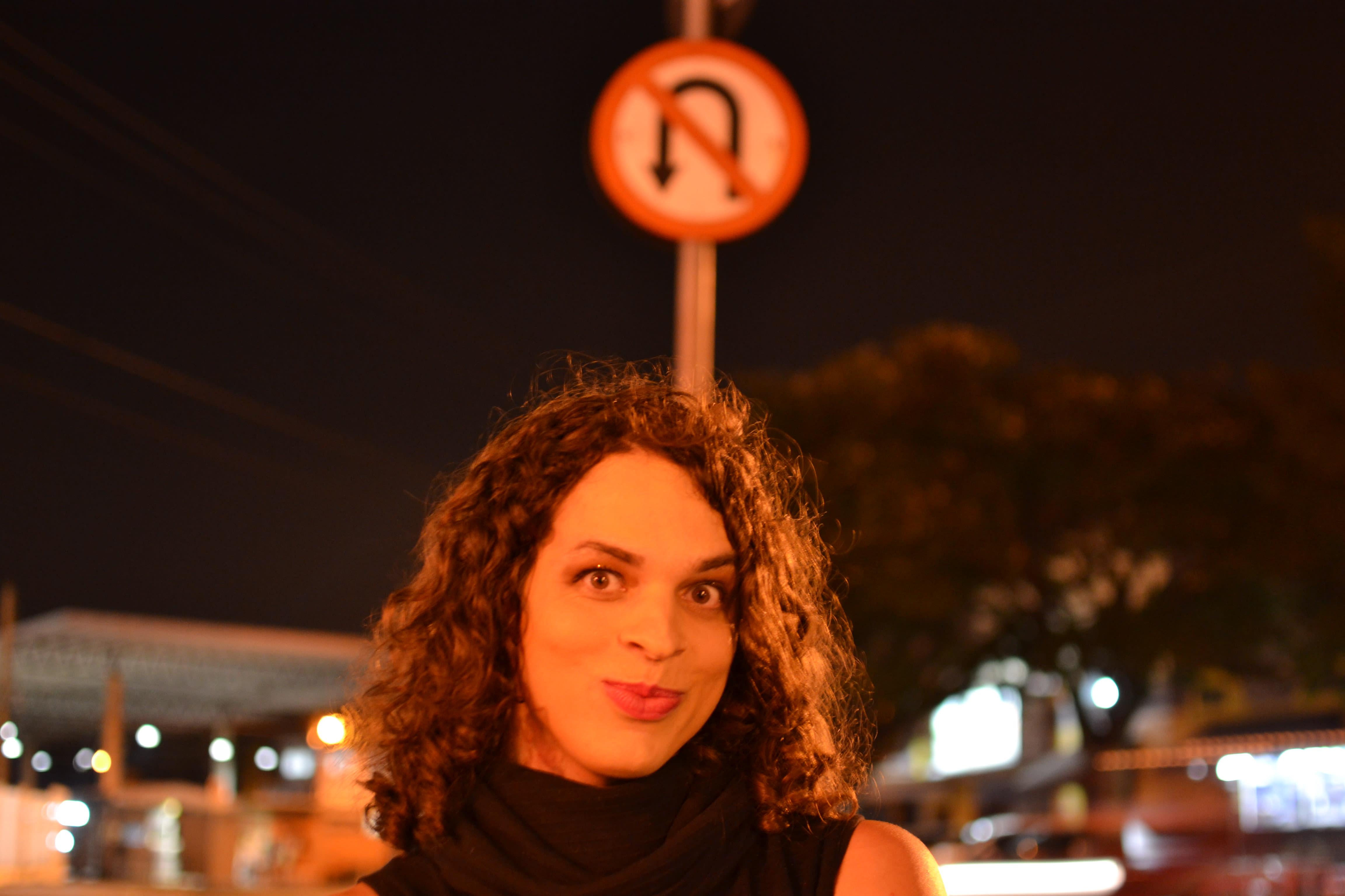 Foto de Amara Moira. Ela está de frente, tem cabelos soltos até os ombros e sorri. Ela está na rua, diante de uma placa de sinalização de trânsito.