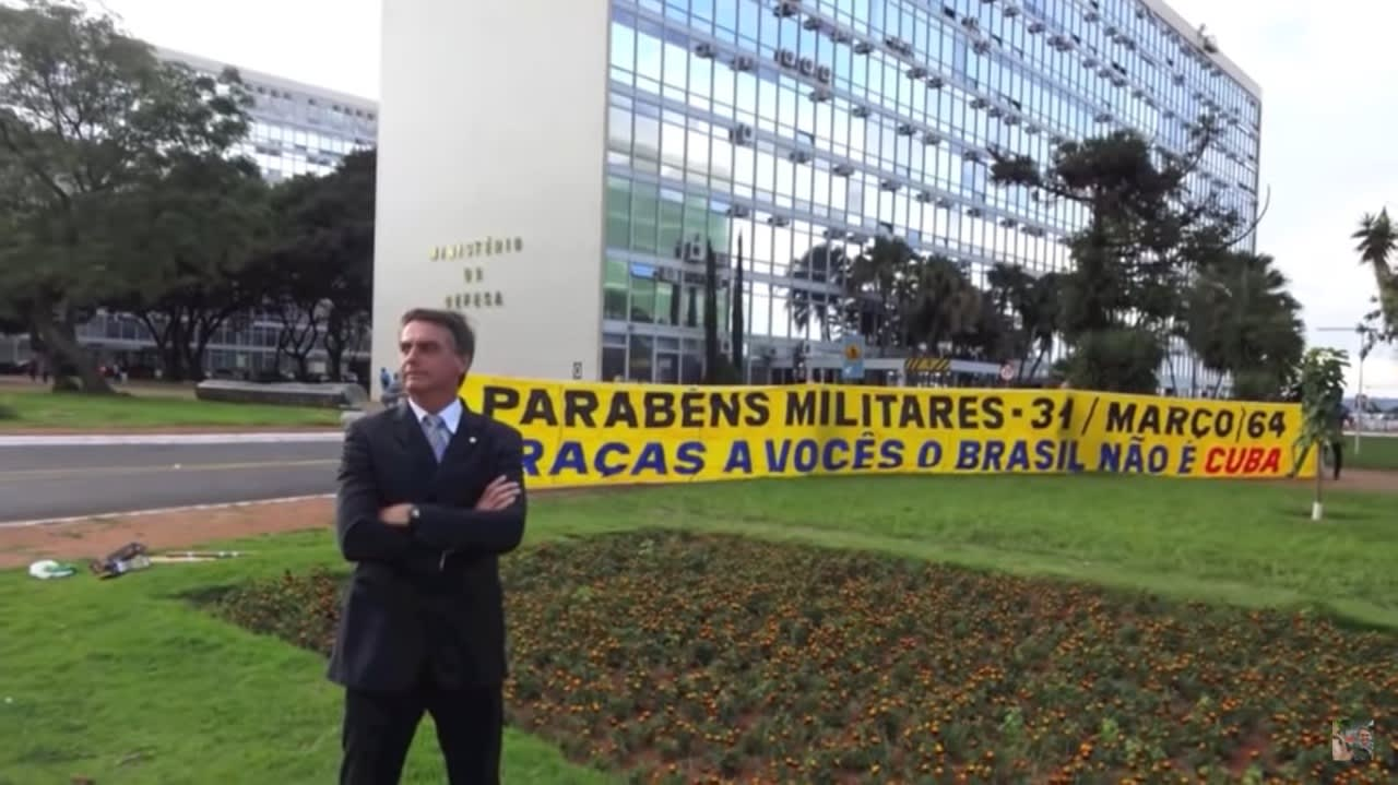 Bolsonaro  na frente de uma faixa com os dizeres: Parabéns militares - 31/Março/64. Graças a vocês o Brasil não é Cuba.