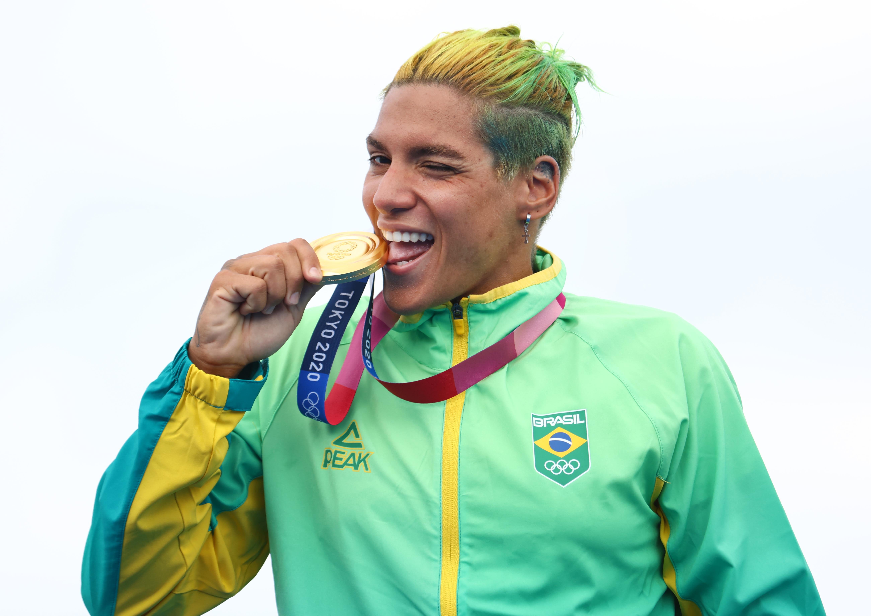 Ana mordendo a medalha de ouro, enquanto pisca para a câmera.