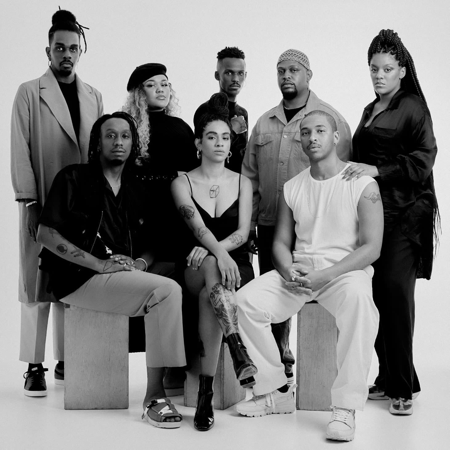 8 pessoas estão pousando para foto em grupo, 5 em pé e 3 sentados à frente. Todos estão olhando pra câmera com serenidade.