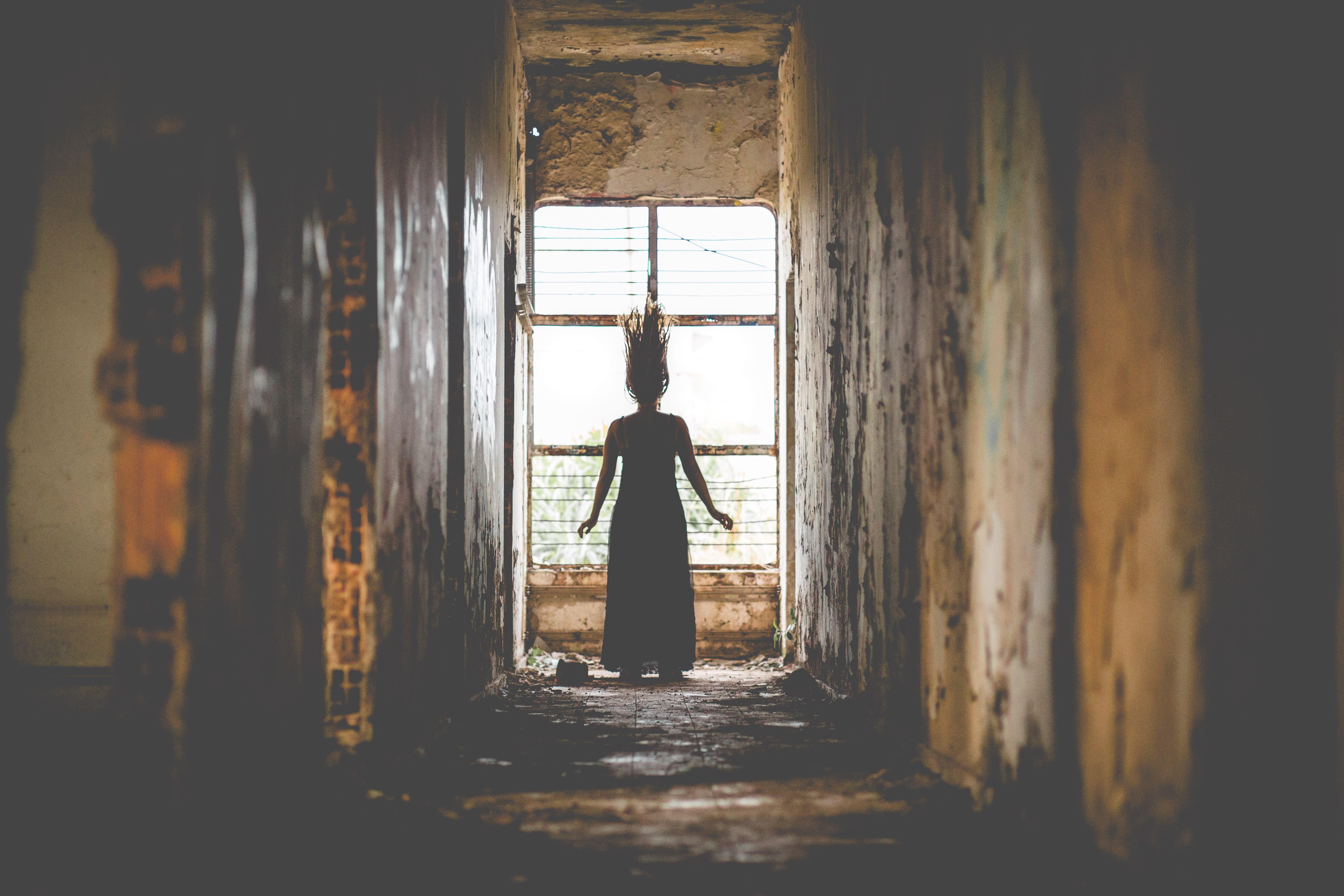 A silhueta de uma mulher, de cabelos arrepiados, em um lugar abandonado.