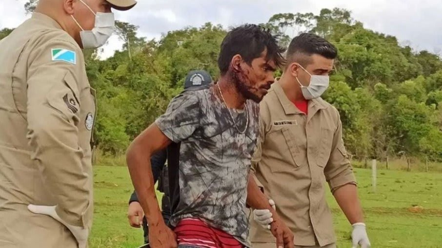 Homem confundido com lázaro sendo atendido por bombeiros. Seu rosto está sangrando.