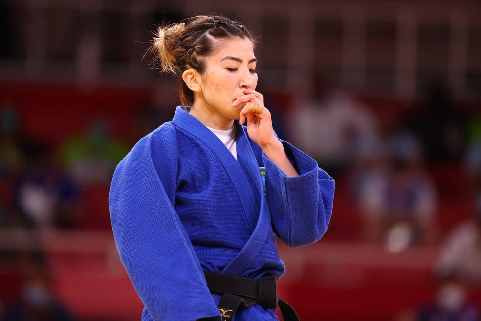 A imagem mostra a atleta Gabriela Chibana na olimpíada. O fundo, onde está a arquibancada, está vazio. No foco, vemos a atleta vestindo um kimono azul, com uma faixa preta. Sua mão está na boca e olhos fechados, sua expressão é de preocupação.
