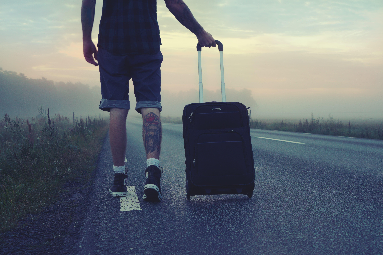 Um homem na estrada com uma mala