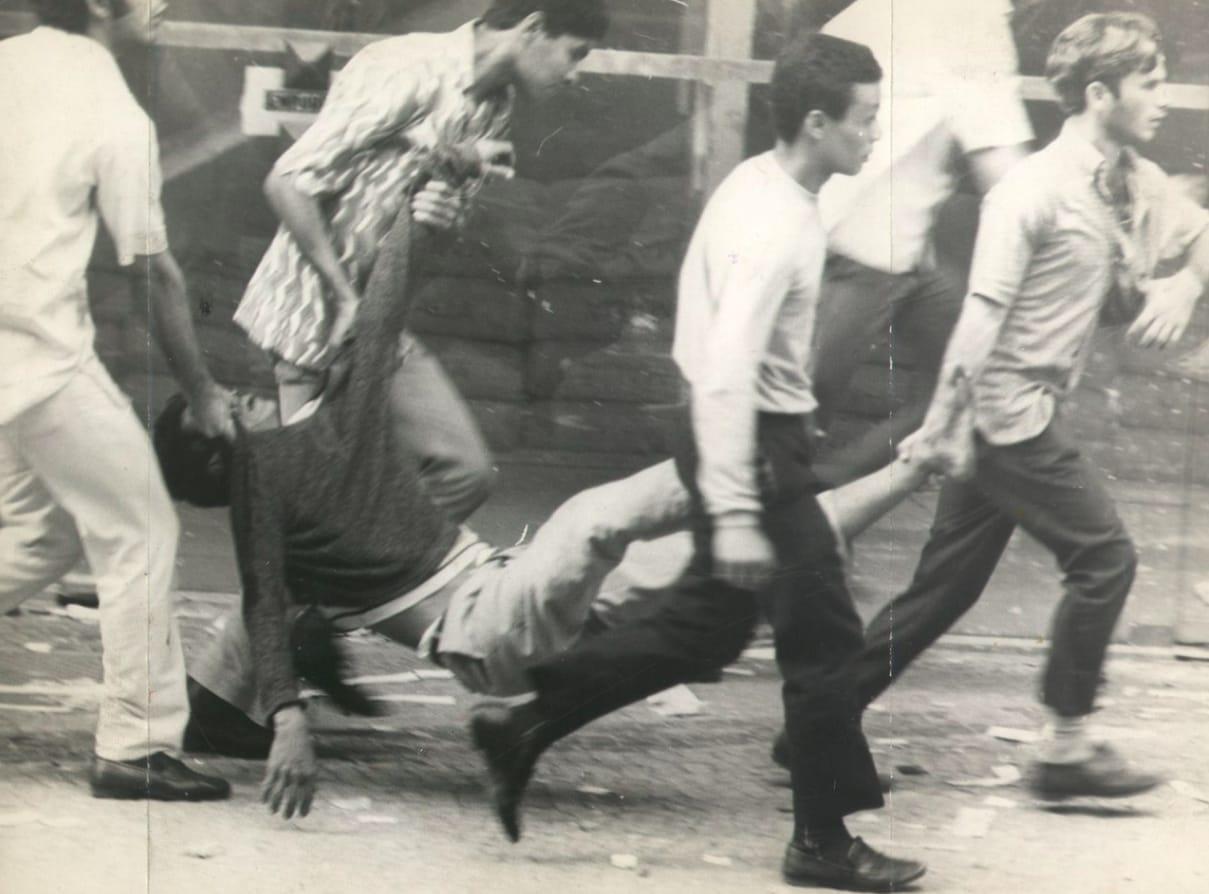Homem sendo carregado após ferimentos em protesto de 1968.