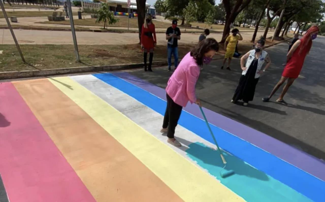 Mulher pintando faixa de pedestres com as cores da bandeira LGBTI+.