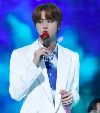 Jin has light brown hair and wears a white suit, he holds a fake rose and is kissing it; his other hand holds a pink sparkly mic