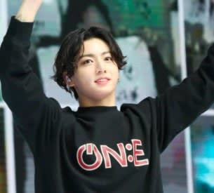 Jungkook waves his hands while wearing a sweater; his hair is dark