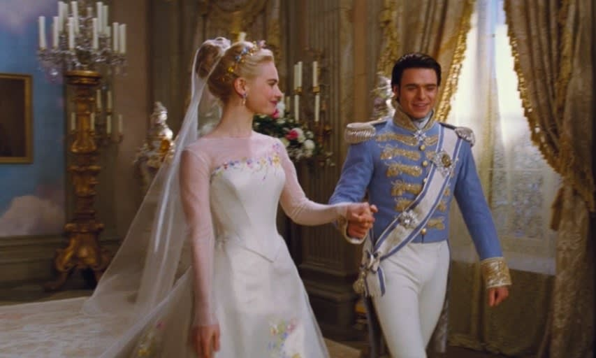 Cinderella wears a wedding gown and smiles at the prince