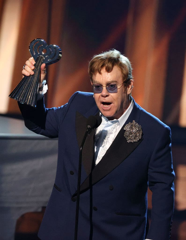 Elton holding an award onstage