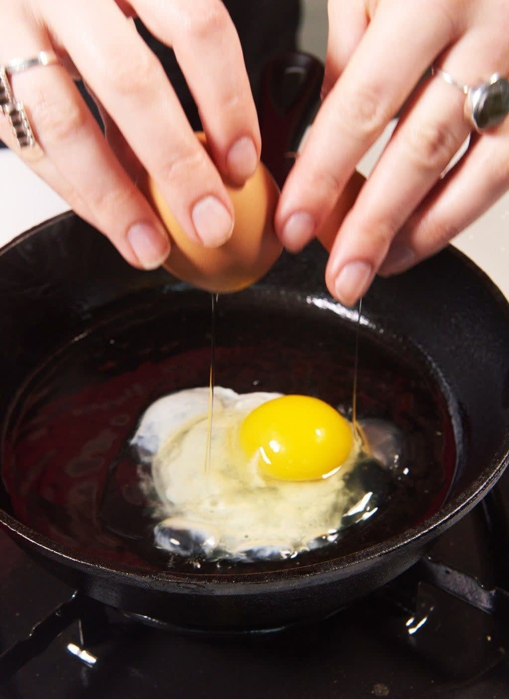 Cracking an egg into a frying pan.