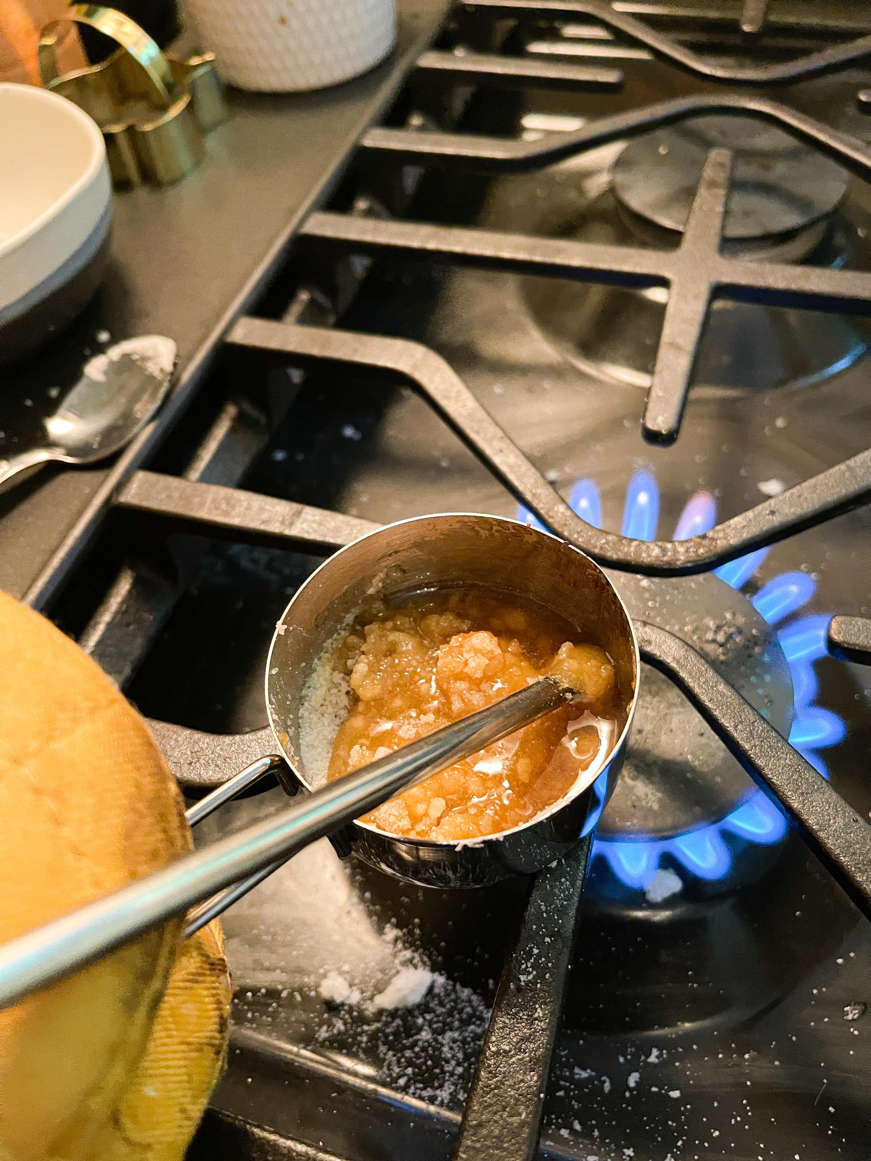 Sugar cooking in metal measuring cup; beginning to caramelize