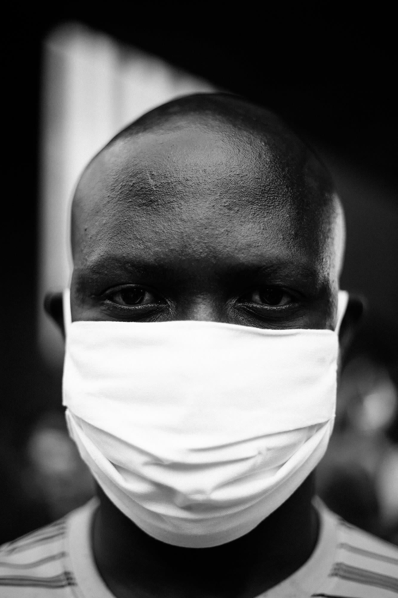 Rosto em close de homem negro com máscara branca olhando na direção da foto.