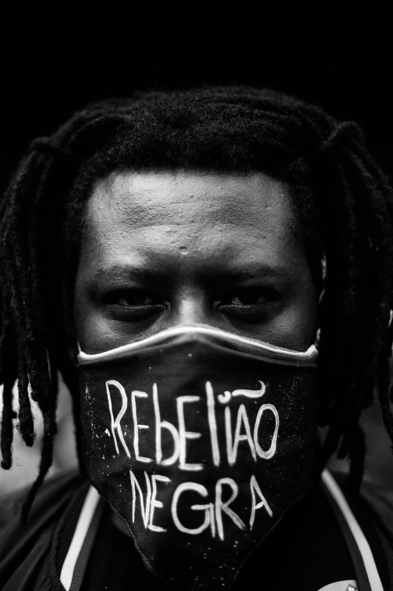 Close de rosto de homem negro usando máscara REBELIAO NEGRA.